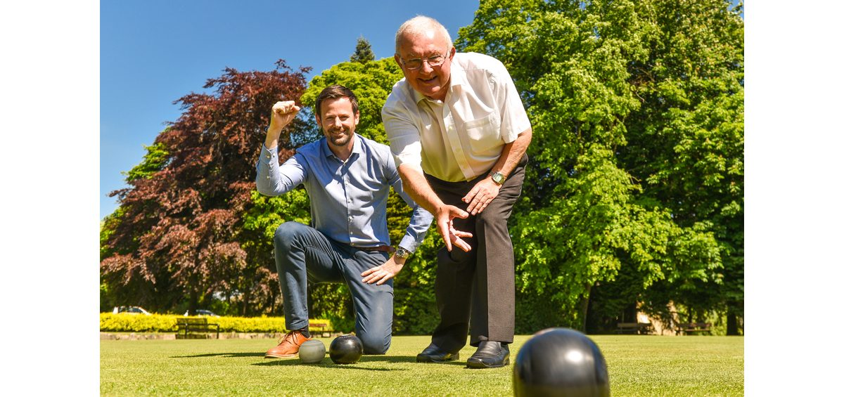 two smiling men bowling