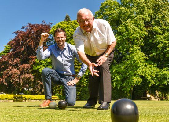 two smiling men bowling