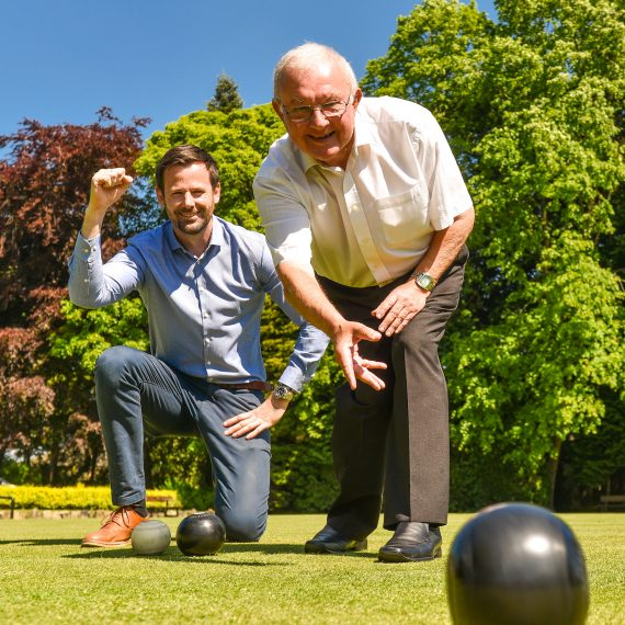 two men play bowls on a green
